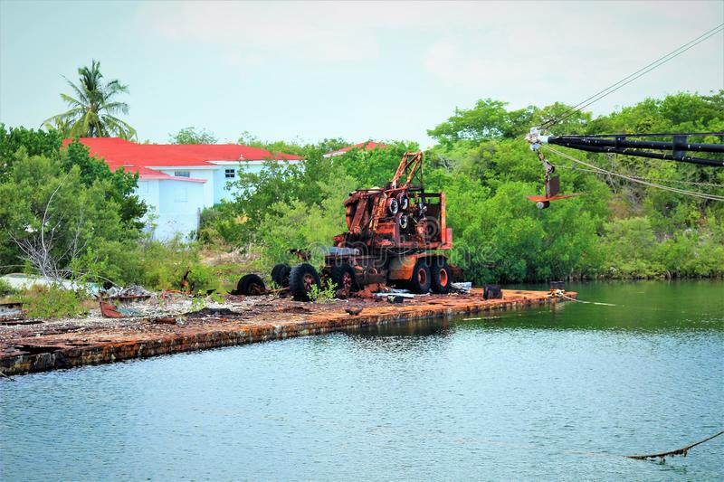 Old work barge with what`s left of a crane rotting away on the deck stock photo