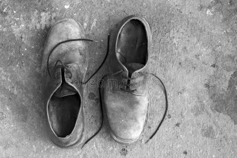 Old work shoes. Two old shoes placed in the opposite direction and seen from above. Black and white. copy space royalty free stock photography