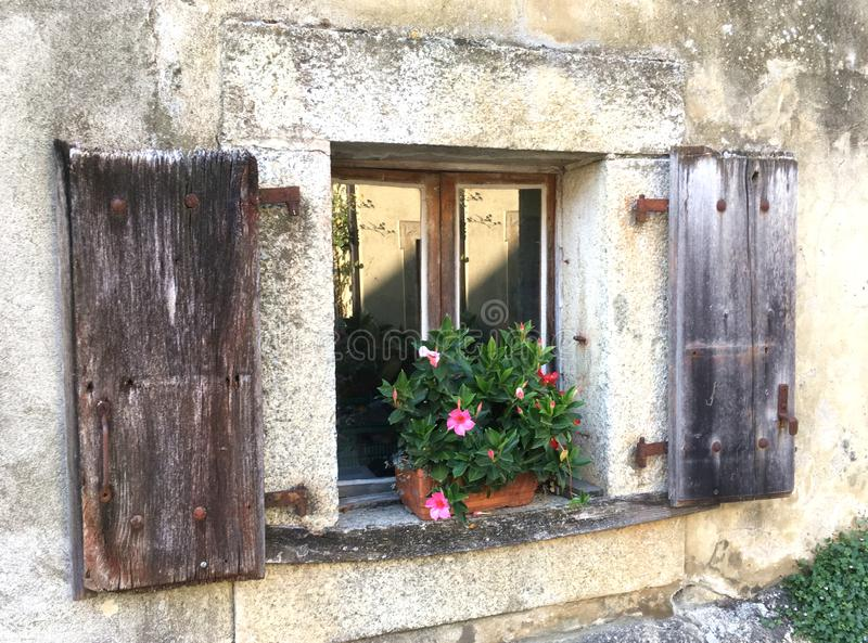 Old World  Farm House Window with Flowers. A classic image from Vaud, Switzerland of a decorated window with a geranium pot of red and white flowers. The window stock photo
