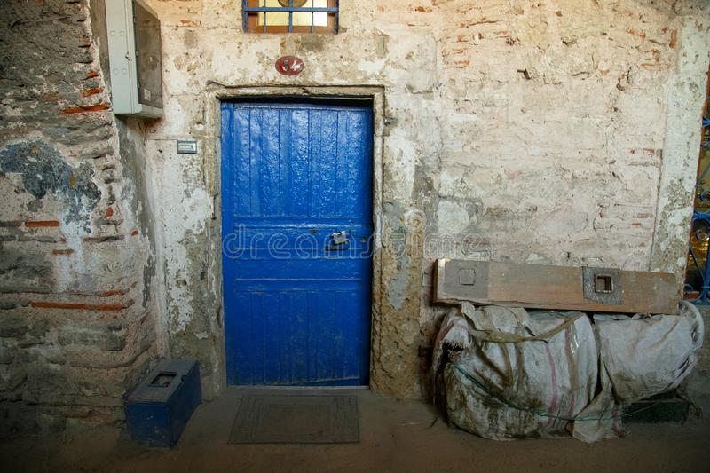 Old and worn blue wooden door with ironwork. Rustic blue door entrance to an old stone house.  stock photo