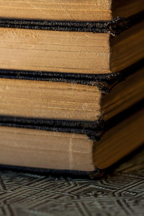 Old worn books stacked on textured surface close up stock photo