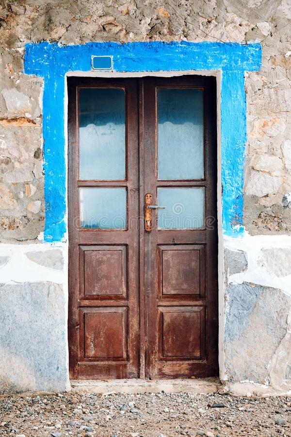 Old worn brown wooden windowed door of a vintage stone house. In Bodrum, Turkey stock images