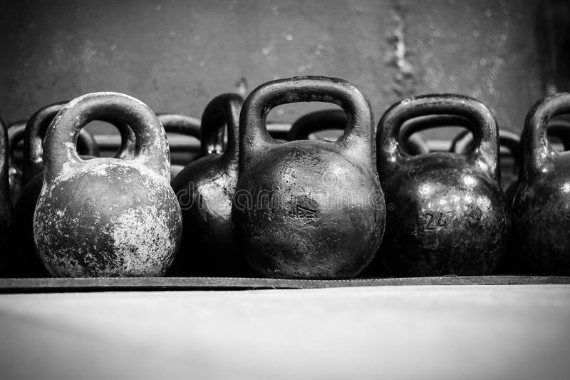 Old worn dumbells in gym. In black and white stock photography