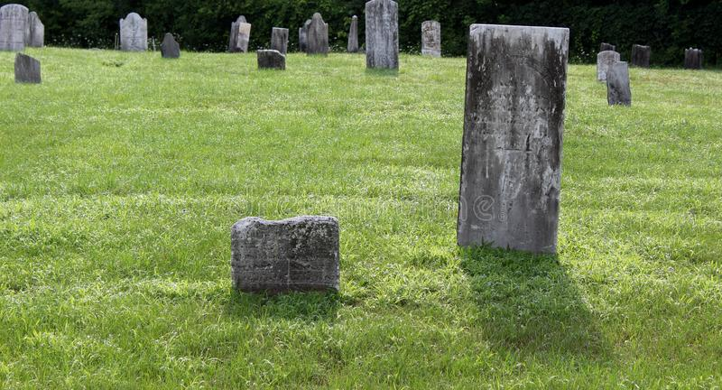 Old worn gravestones in historic Gideon Putnam Cemetery, Saratoga Springs, New York, 2018. Old, weathered headstones seen with manicured lawns inside the stock photography