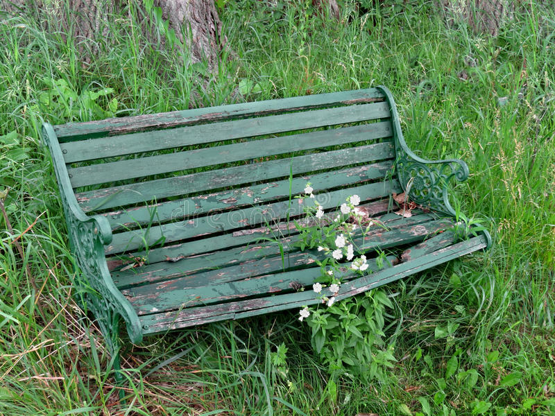 Old and worn green bench in weeds. stock photos