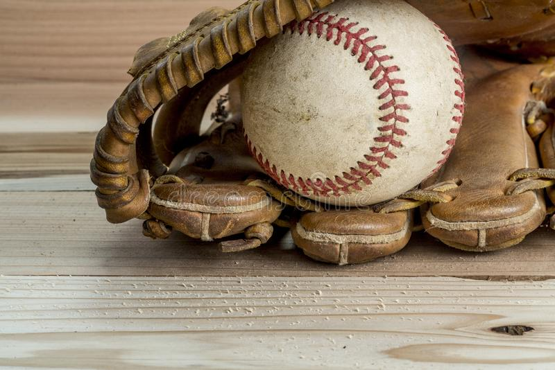 Old worn leather baseball glove and used ball on a wooden royalty free stock images