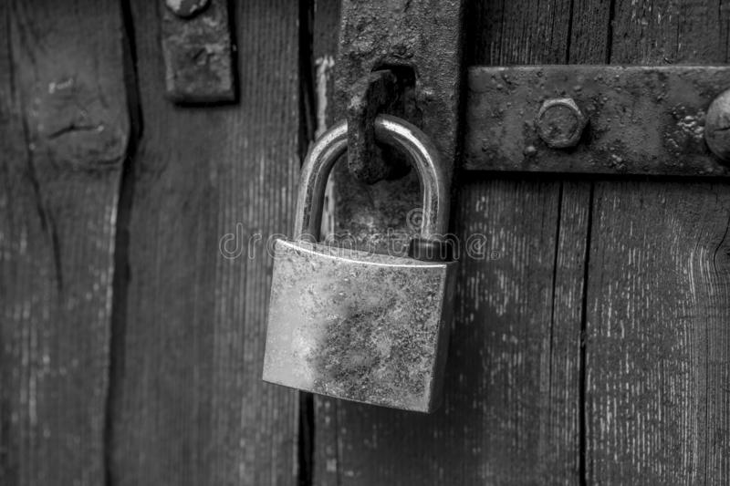 old weathered lock on a collapsing wooden door stock image