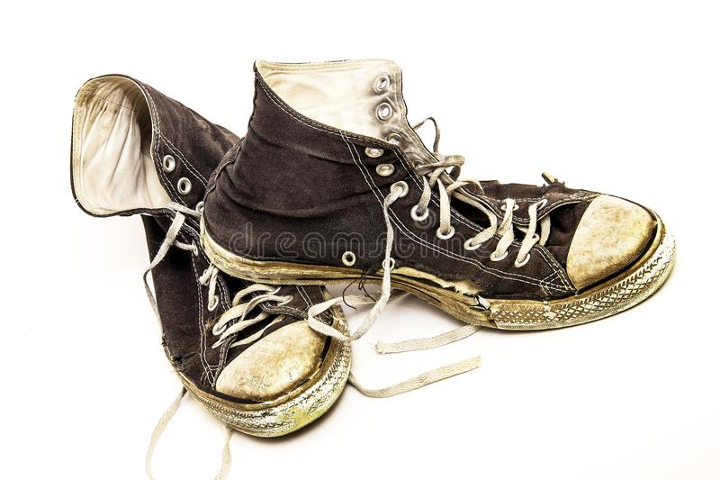 Old worn out pair of old black and white high top tennis shoes on white background royalty free stock photos