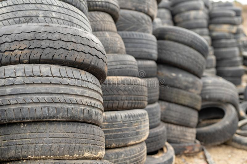 Old worn out tires on an abandoned trash dump. Garbage heap ready for disposal. Season of the spring stock photo