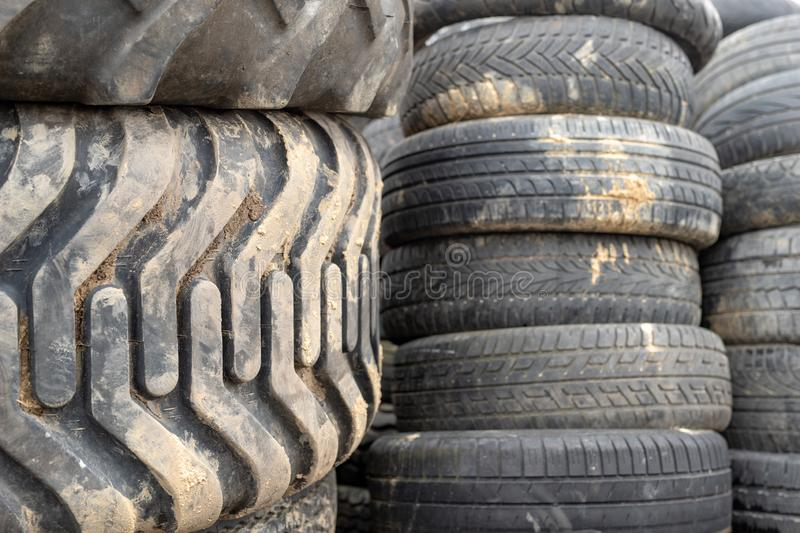 Old worn out tires on an abandoned trash dump. Garbage heap ready for disposal. Season of the spring stock image