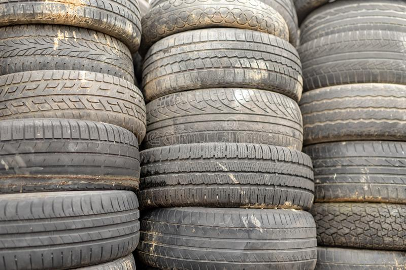 Old worn out tires on an abandoned trash dump. Garbage heap ready for disposal. Season of the spring stock photography