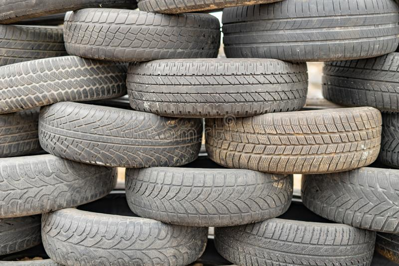 Old worn out tires on an abandoned trash dump. Garbage heap ready for disposal. Season of the spring royalty free stock images