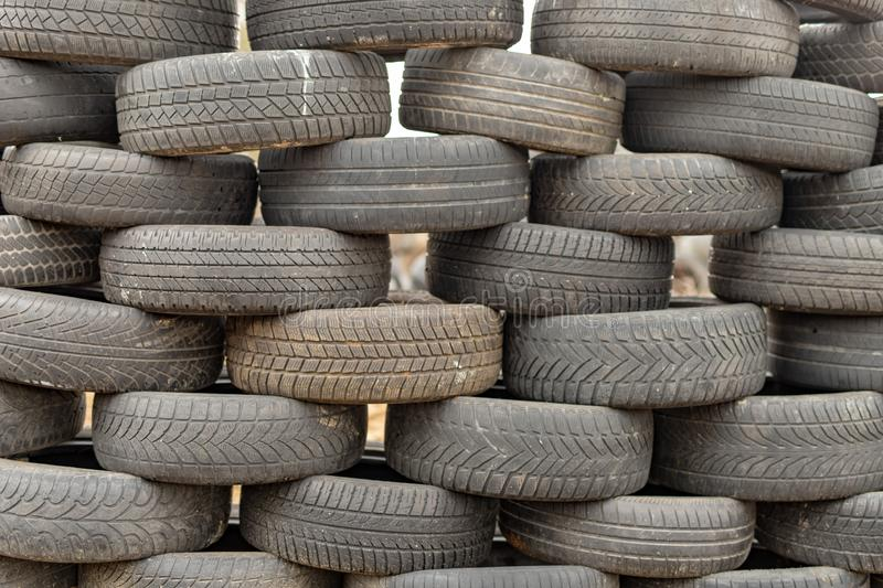 Old worn out tires on an abandoned trash dump. Garbage heap ready for disposal. Season of the spring royalty free stock image
