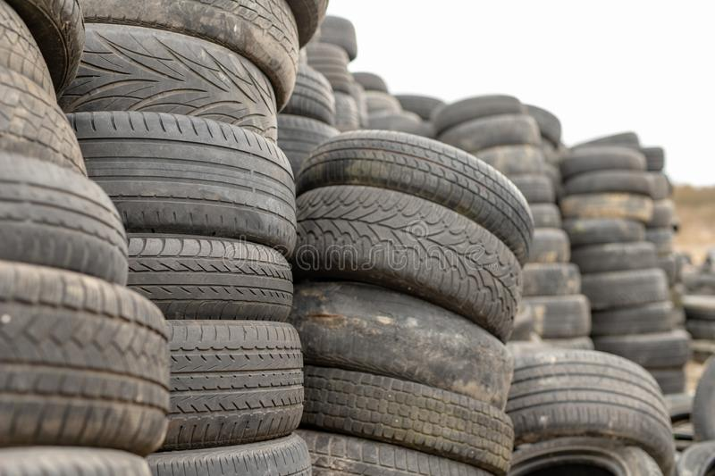 Old worn out tires on an abandoned trash dump. Garbage heap ready for disposal. Season of the spring royalty free stock photo