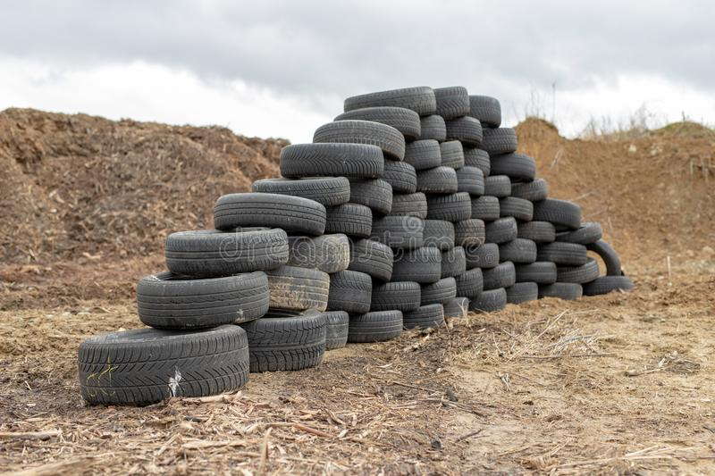 Old worn out tires on an abandoned trash dump. Garbage heap ready for disposal. Season of the spring stock photos