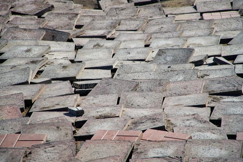 Old worn pavement tiles in the process of dismantling and replacement. Urban economy stock photography