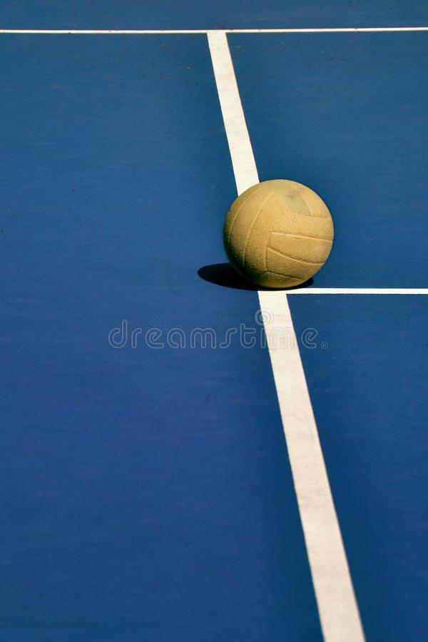 Old and Worn Volleyball on Court. An old and yellow volleyball on the white lines of a blue volleyball court royalty free stock photo