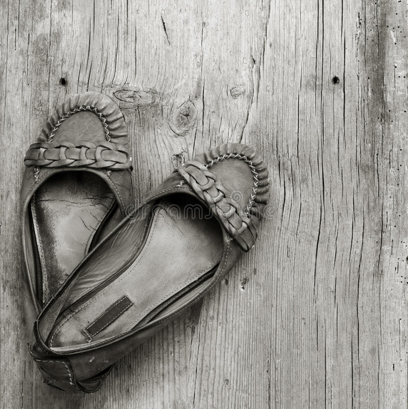 Old worn women's shoes made of genuine leather on old gray wooden board in the cracks, top view close-up stock images