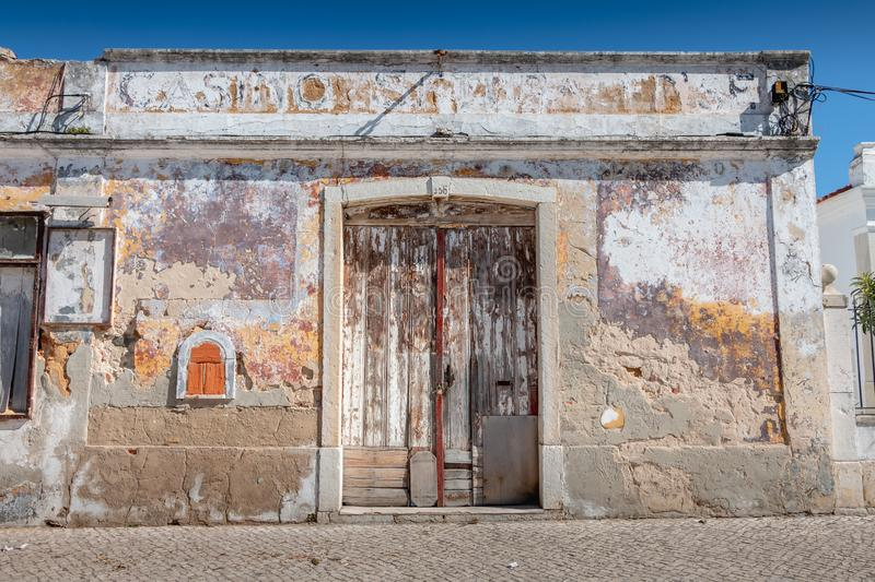 Old worn wooden door on a ruined building in the center of Setubal stock photo