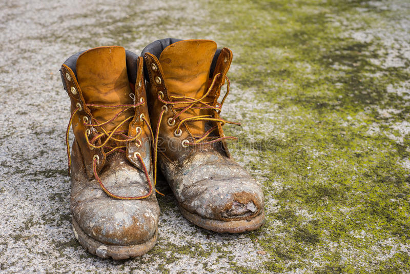 Old worn work boots. On grungy dirty ground background stock image