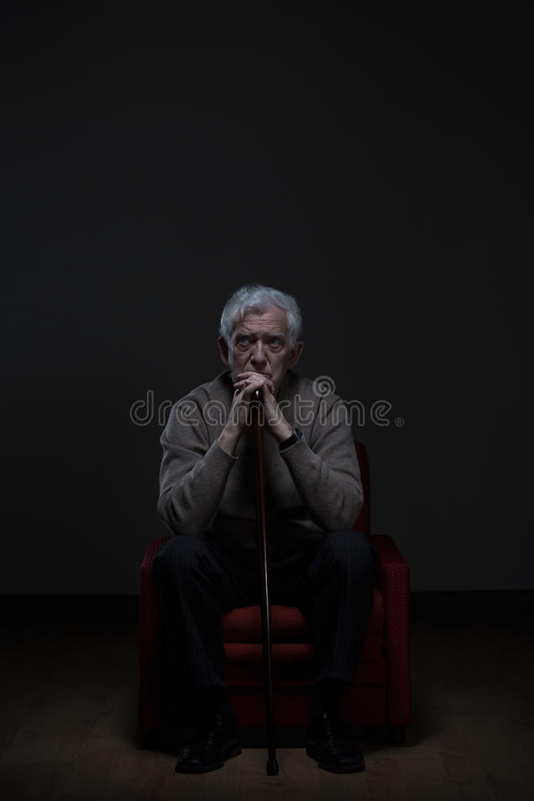 Old worried man with cane. Old man with worried face sitting alone and holding cane stock image