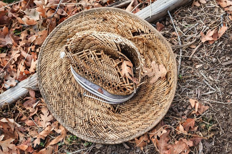 An old woven straw hat on a bed of brown autumn leaves. stock photo