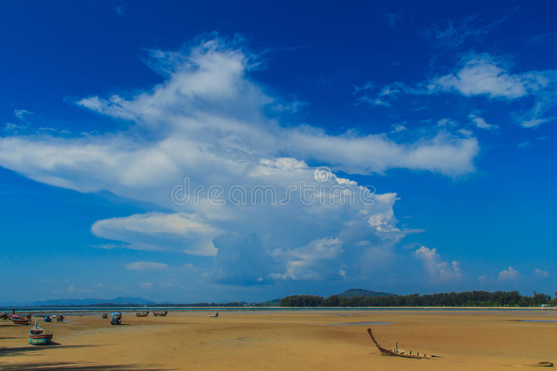 Old wreck fishing boat buried in the sand with blue sky on cloud. Y day background royalty free stock photo