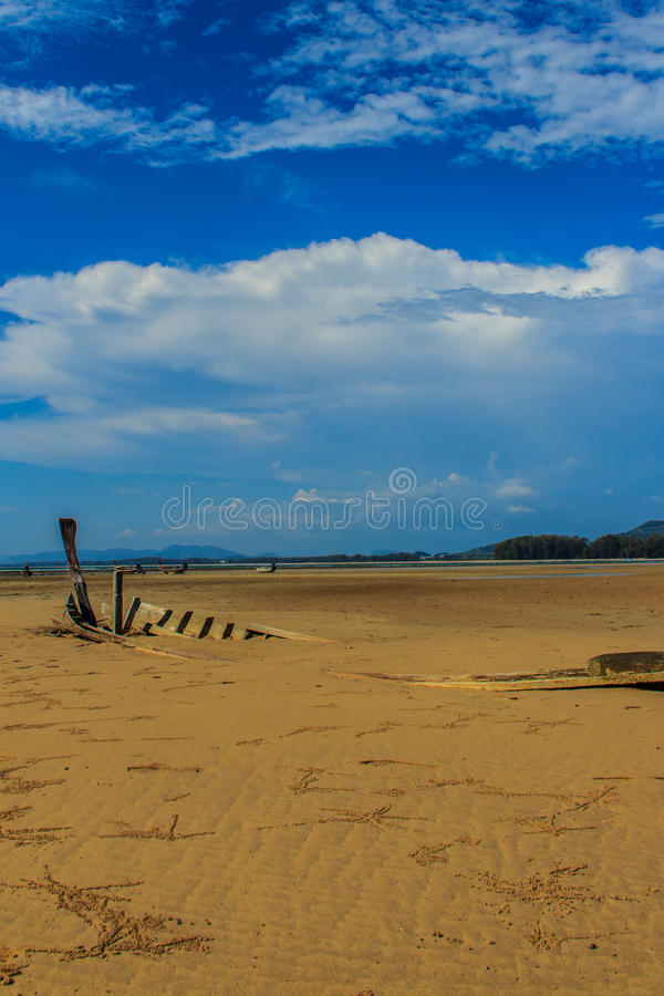 Old wreck fishing boat buried in the sand with blue sky on cloud. Y day background stock image