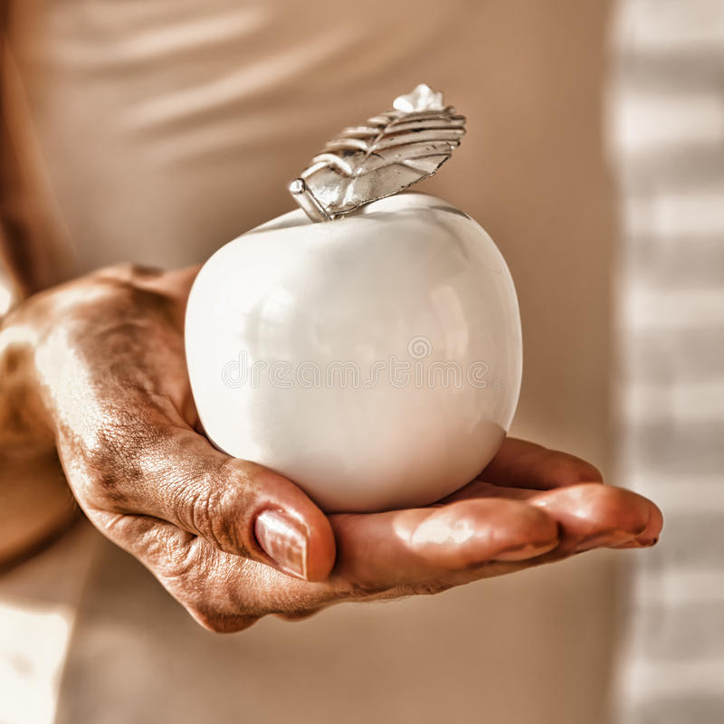 Old wrinkled hand reaches the apple of youth royalty free stock image
