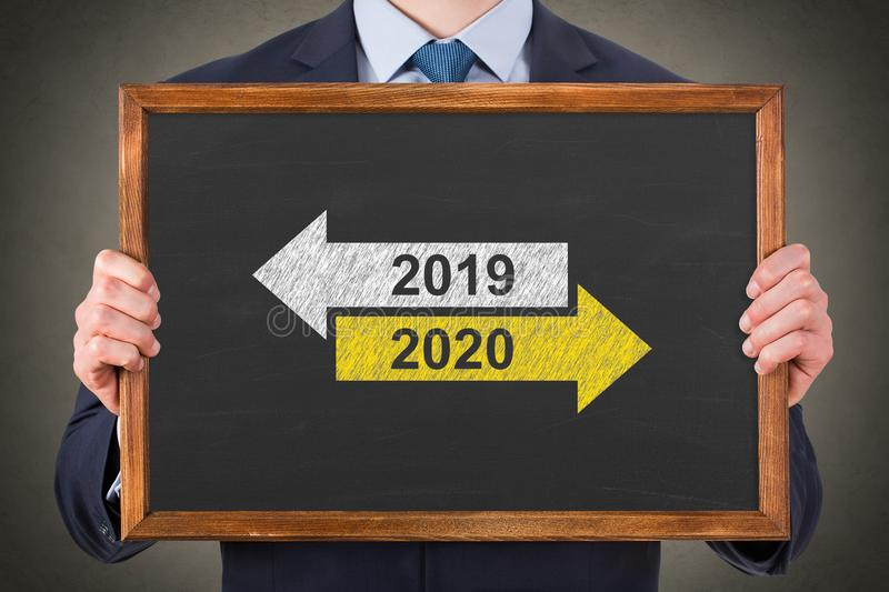 Old Year New Year 2020 over on Blackboard Background royalty free stock photo