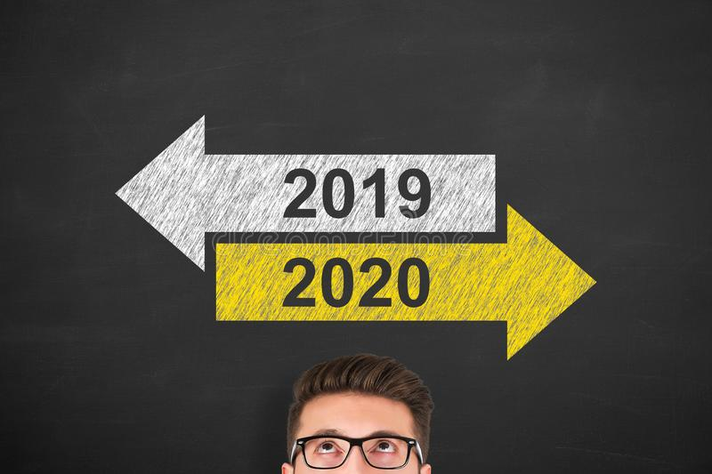 Old Year New Year 2020 over Human Head on Chalkboard Background royalty free stock photography
