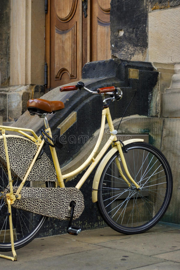 Old yellow bicycle. leather seat with shock absorbers and wheel in front of a church royalty free stock images