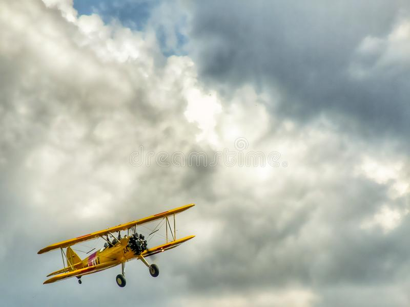 Old yellow biplane aircraft on colorful cloudy sky. stock photos