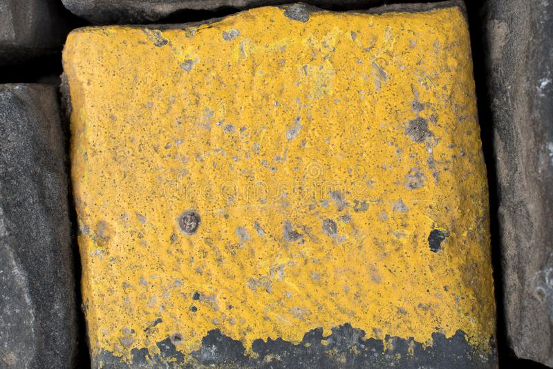 Old yellow and black granite road cubes or cobbles as background or wallpaper. Vertical image. stock image