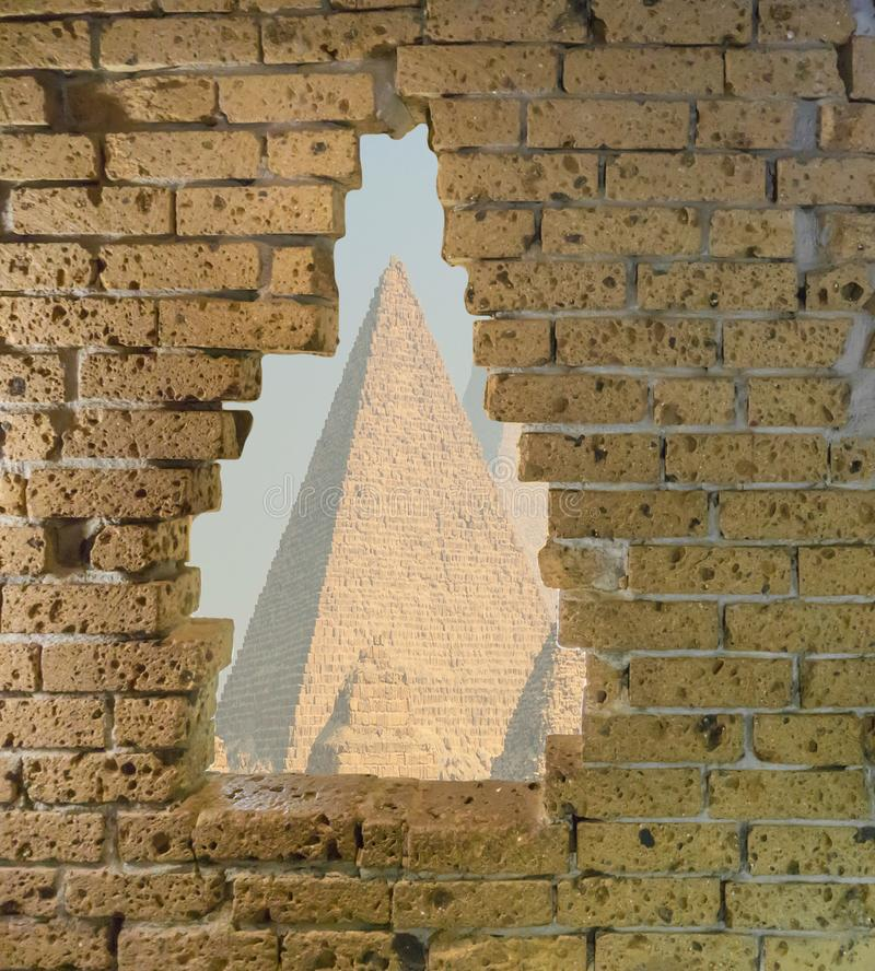 Old yellow brick wall in ruins with a big opening in it viewing on some egyptian pyramids stock photos