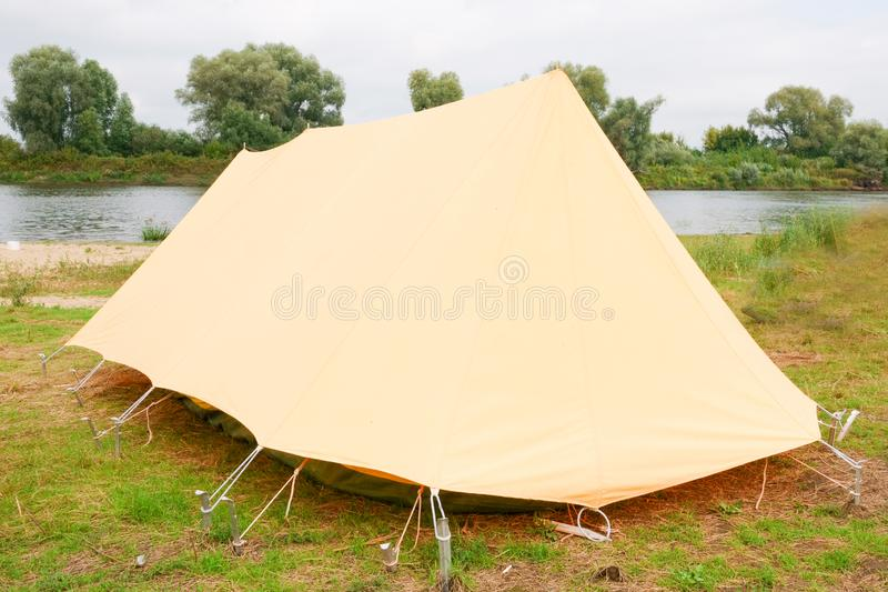 Old yellow canvas camping tent with iron pegs. Old yellow canvas camping tent, vintage, grass, holiday, nature, outdoors, rural, shelter, travel, vacation stock photos