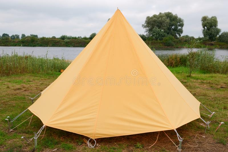 Old yellow canvas camping tent with iron pegs. Old yellow canvas camping tent, vintage, grass, holiday, nature, outdoors, rural, shelter, travel, vacation stock photography