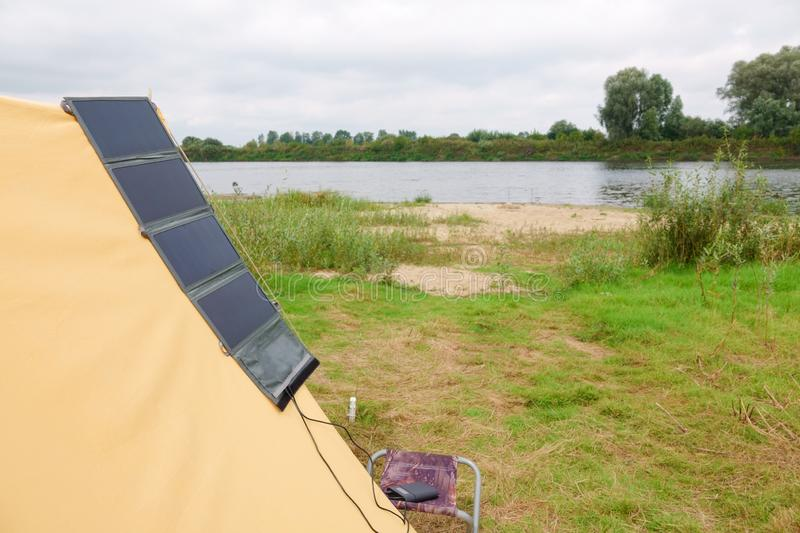 Old yellow canvas camping tent with solar panels. Old yellow canvas camping tent, vintage, grass, holiday, nature, outdoors, rural, shelter, travel, vacation stock photo