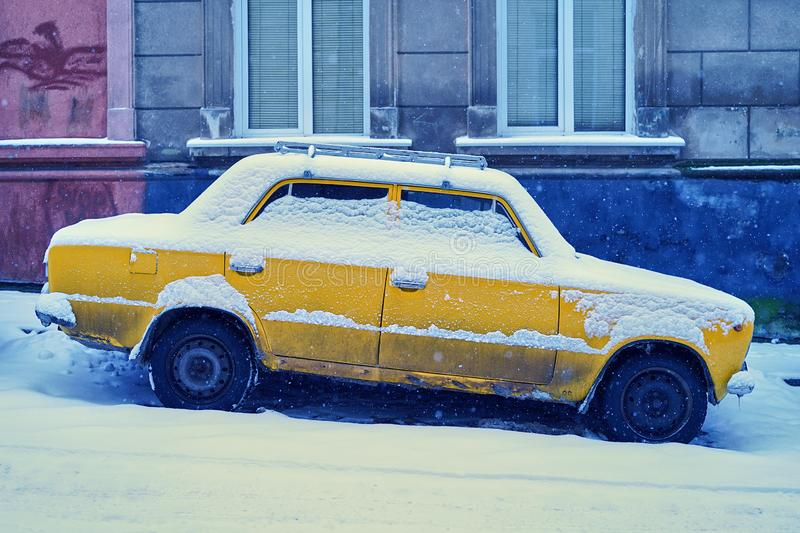 Old yellow car covered with snow parked on a snowy sloping street in winter city royalty free stock photography