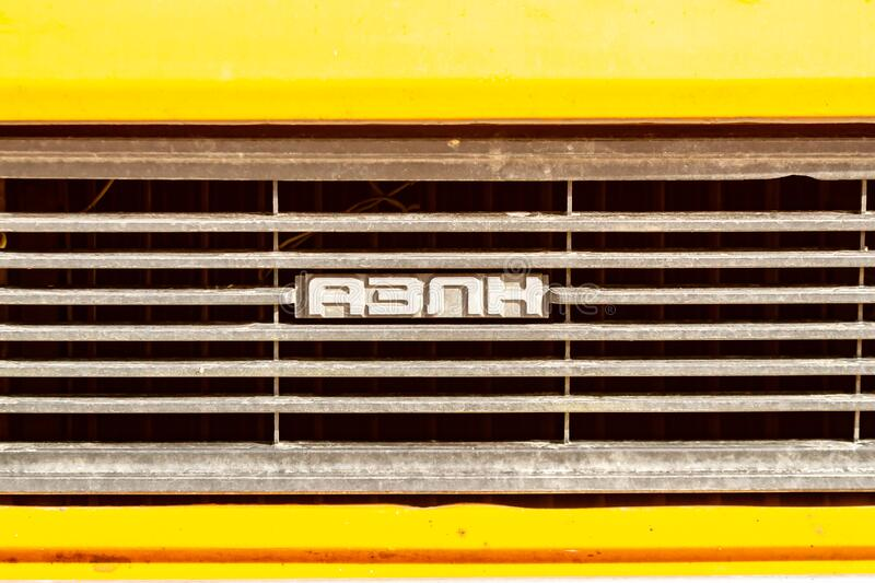 Old yellow car radiator grill with four Russian letters AZLK. Close-up. Horizontal orientation. High quality photo stock image