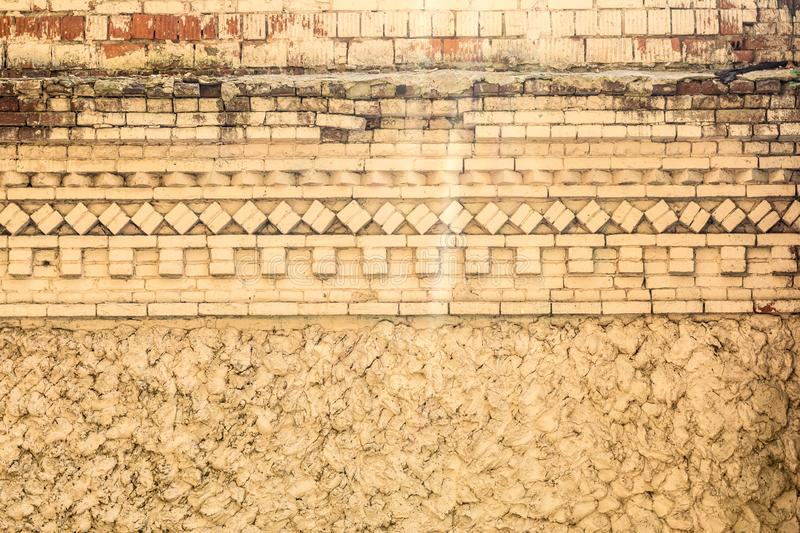 Old yellow concrete wall with rough relief stucco and ornament of brickwork, architecture abstract background royalty free stock photos