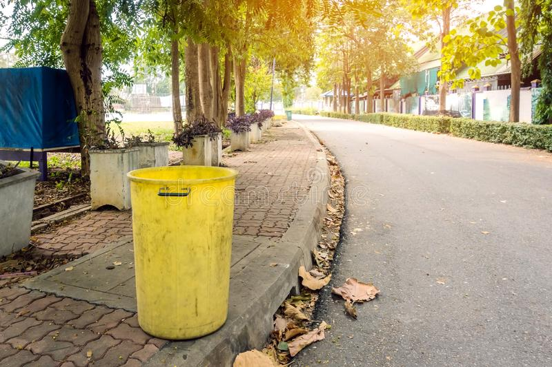 An old yellow dustbin in the public park beside the walk way royalty free stock photography