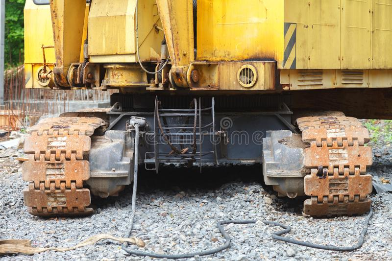 An old yellow excavator crane stands on gravel. An old, rust-caterpillar crane stands on a gravel on a construction site on a sunny day. Close-up royalty free stock photography