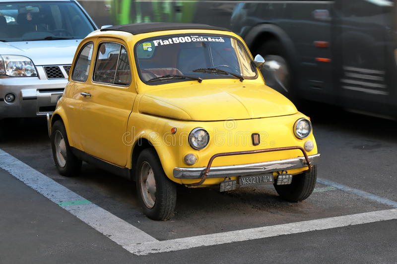 Old yellow Fiat 500 parked on street in Rome, Italy. royalty free stock image