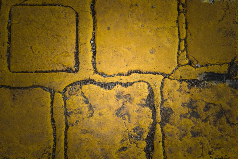 Old yellow granite road cubes as background or wallpaper. Dark edges. Old road yellow cobbles stock photo
