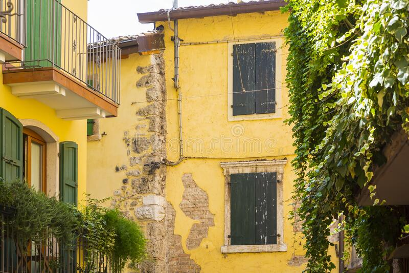 Old yellow house facade, green window shutters and balcony stock photos