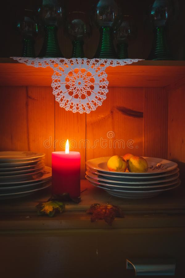 Old yellow painted cupboard with candles, autumn leaves and crocheted doilies. View of an old yellow painted wooden vintage cupboard with crocheted white doilies royalty free stock photography