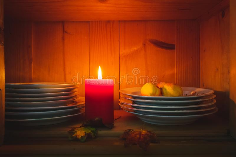 Old yellow painted cupboard with candles, autumn leaves and crocheted doilies. View of an old yellow painted wooden vintage cupboard with crocheted white doilies royalty free stock photo