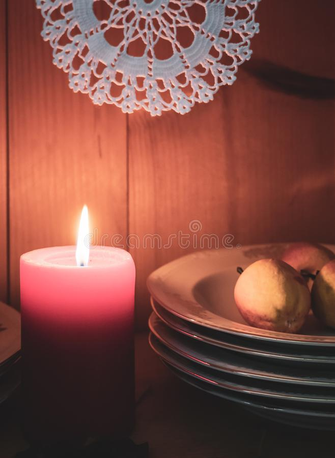 Old yellow painted cupboard with candles, autumn leaves and crocheted doilies. View of an old yellow painted wooden vintage cupboard with crocheted white doilies royalty free stock image
