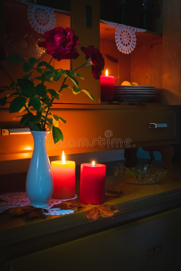 Old yellow painted cupboard with candles, a vase with red roses, autumn leaves and crocheted doilies. View of an old yellow painted wooden vintage cupboard with stock photos